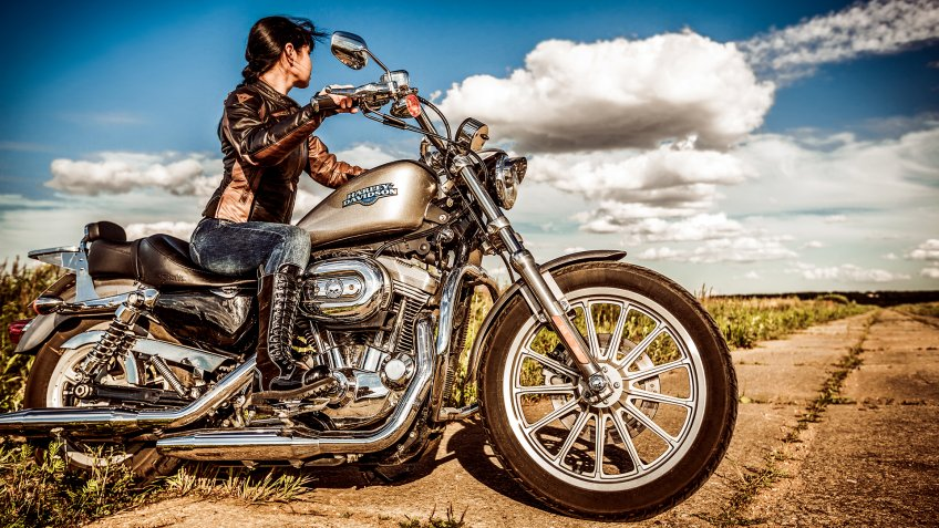 RUSSIA-JULY 7, 2013: Biker girl and bike Harley Sportster.