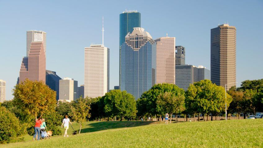"""With a background of beautiful clear blue sky and the modern skyscrapers of the Houston , Texas city skyline this horizontal image has three ladies enjoying a beautiful fall afternoon by walking their dogs and pushing a baby stroller through the park."