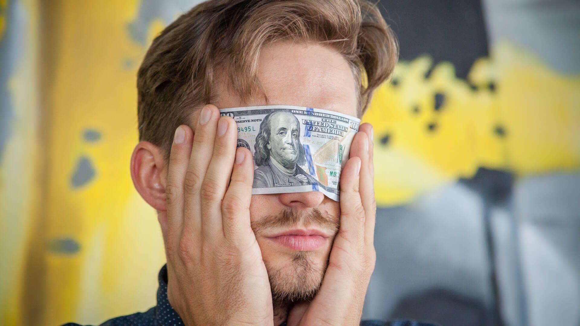 Man blindfolds eyes with 100 dollar bill
