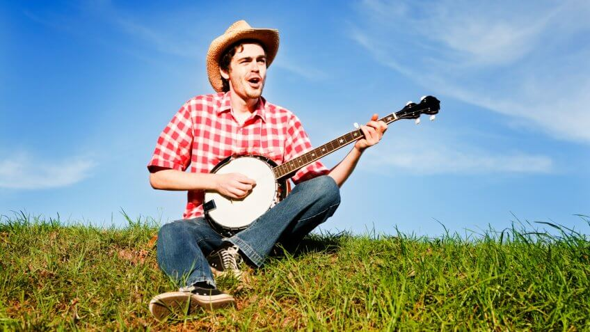 A happy country boy sits on the grass in the sunshine, playing his banjo and singing.