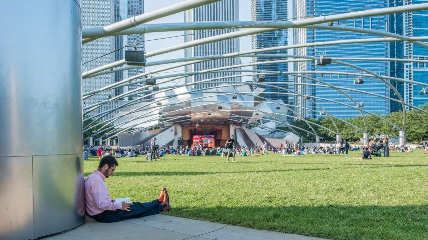 Chicago, IL, July 17, 2017: A young man reads, waiting for an event to begin at Millennium Park in Chicago.