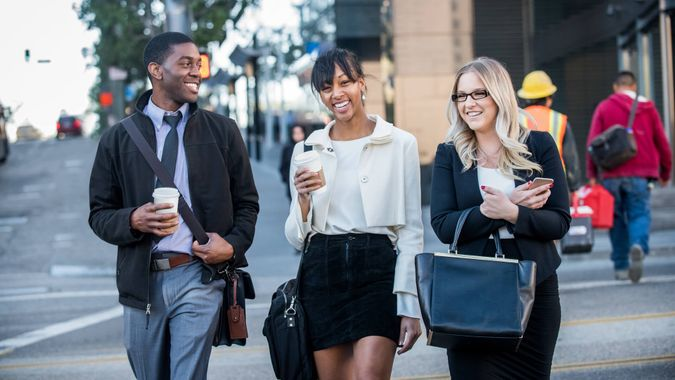 millennial office workers crossing a city street at the end of their work day with coffee.
