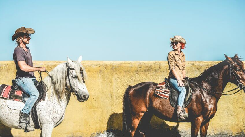Couple riding horses in countryside tour