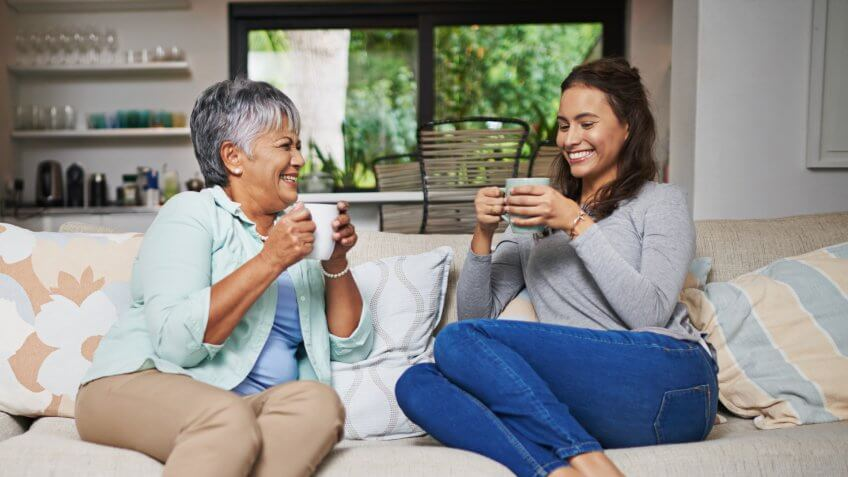 young woman and her mother chatting on the sofa while drinking coffee