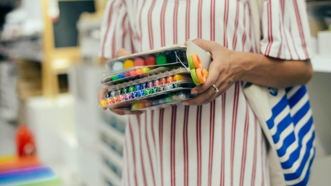 Mother choosing buying stationery in store preparing for first day in school.