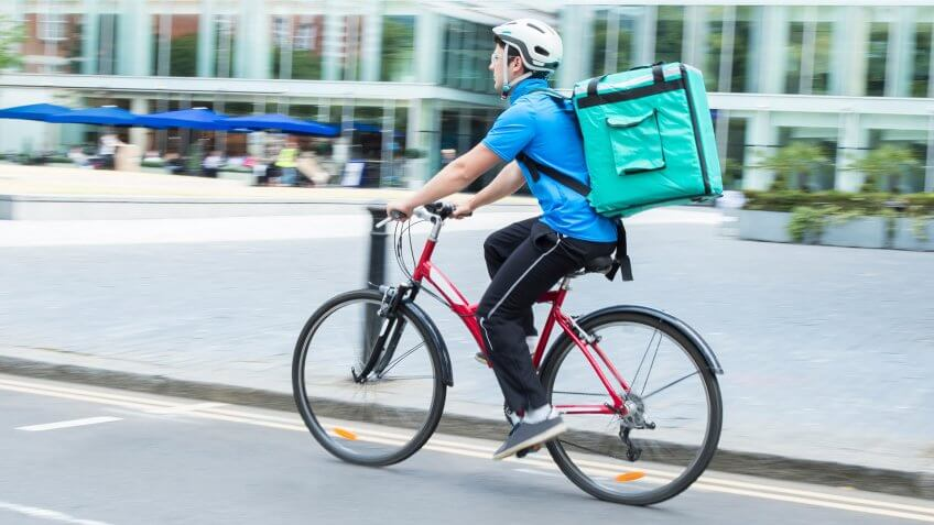 Courier On Bicycle Delivering Food In City.