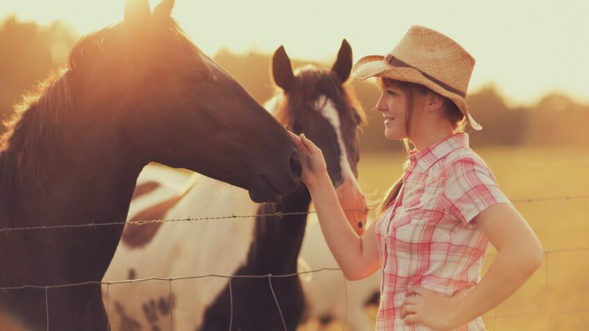 A young western girl spends time with her horses on the farm.