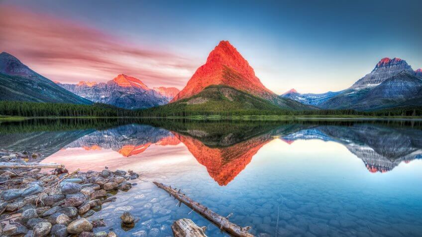 Stunning reflections on Swiftcurrent Lake in northern Montana at sunrise.