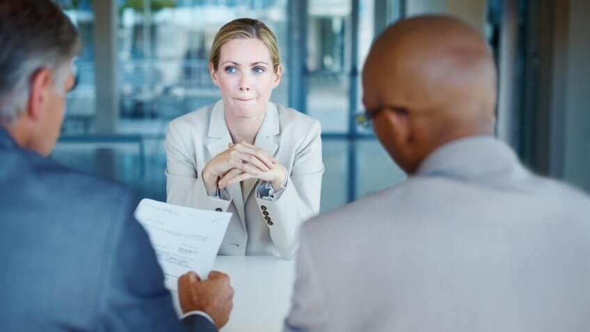 Tensed business woman sitting in front of panel of interviewers.