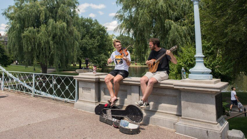 Boston, MA, July 4,2017: On Independence Day, two young friends play music for tips in the famous Boston Public Gardens.