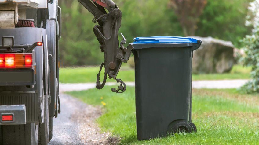 Garbage disposal truck lifting a waste bin