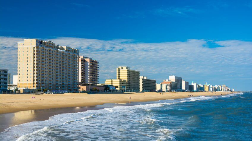 Virginia Beach's coastal skyline with hotels and condominium towers, and with the Virginia Beach coastline and people in the foreground.