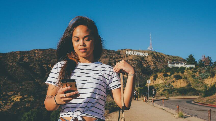 Woman checking text messages as she walks down a hill in California