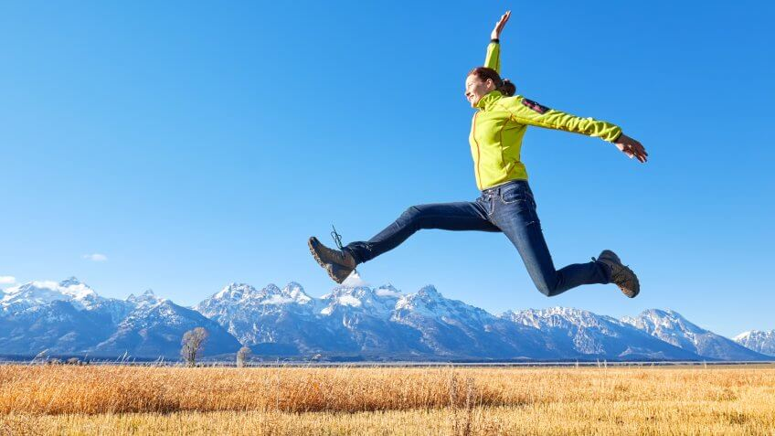 Happy young woman jumping on a meadow, Grand Teton mountain range in distance, Wyoming, USA.
