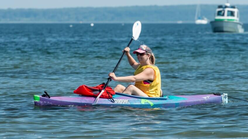 Blonde woman in kayak paddling in charity race across Narragansett Bay, from Newport to Jamestown, Rhode Island.