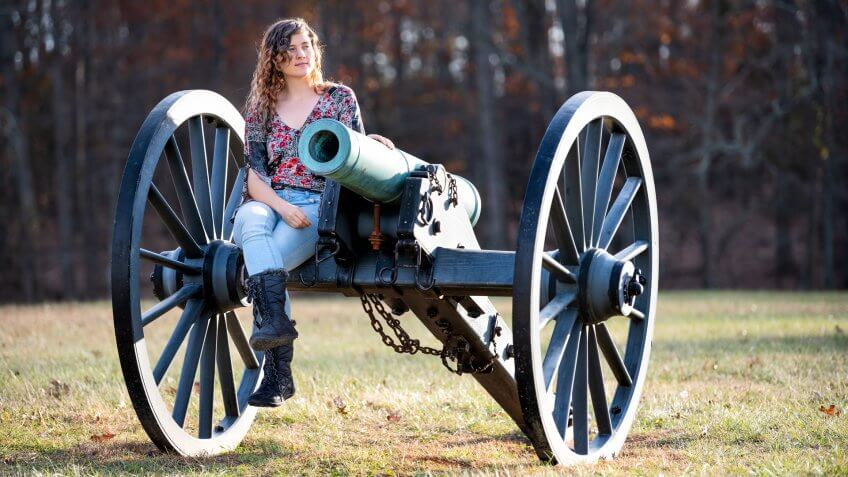 Young woman sitting on old cannon in Manassas National Battlefield Park in Virginia where Bull Run battle was fought