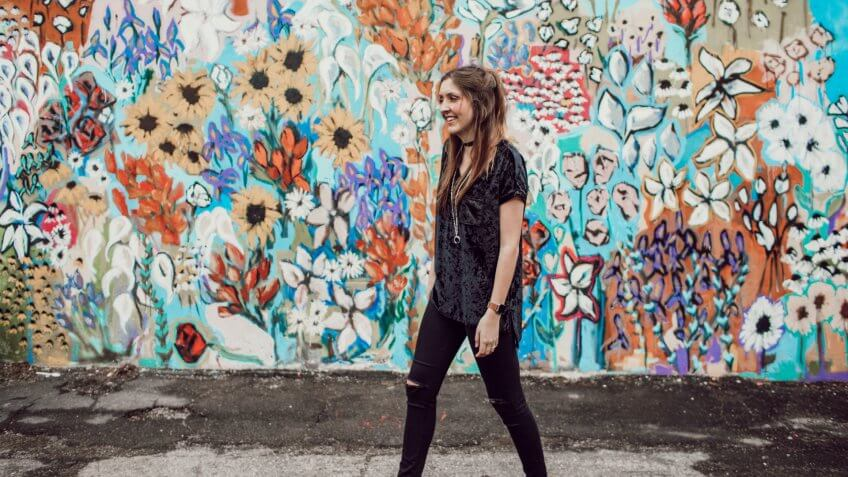 Woman walking past a colorful mural in Tennessee