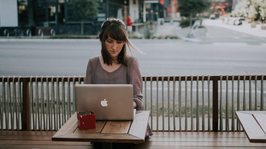 Woman working on laptop at a coffee shop in Texas