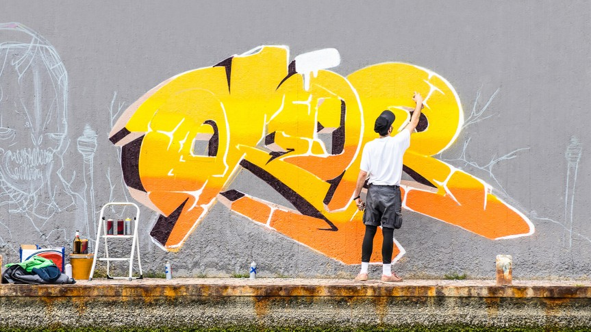 Street artist painting colored graffiti on public space wall - Modern art concept of urban guy performing and preparing live murales paint with yellow aerosol color spray - Cloudy afternoon filter.