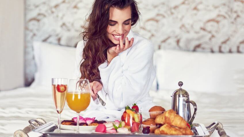 Shot of an attractive young woman enjoying a luxurious breakfast in her room.