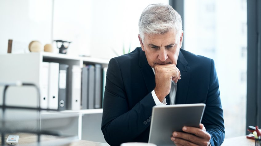 mature businessman using his digital tablet at his desk.