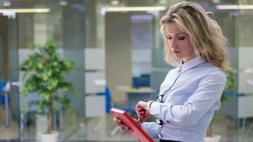 Elegant blonde businesswoman with red notepad in her hand checking time.