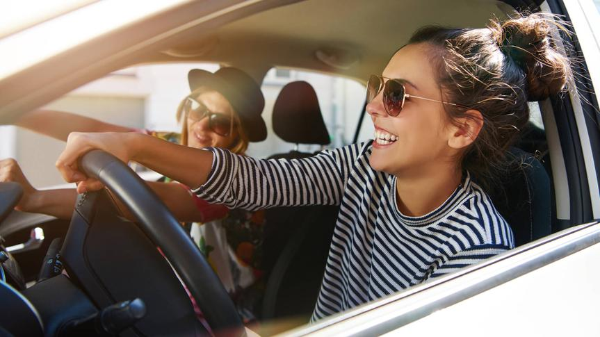 Two attractive young girlfriends wearing sunglasses talking and laughing together while driving in a car through the city on a sunny day.