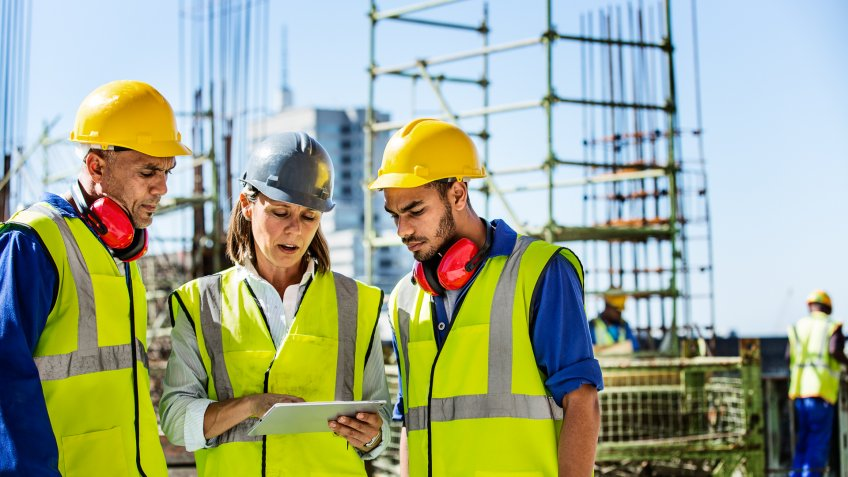 Male and female architects using digital tablet at construction site.