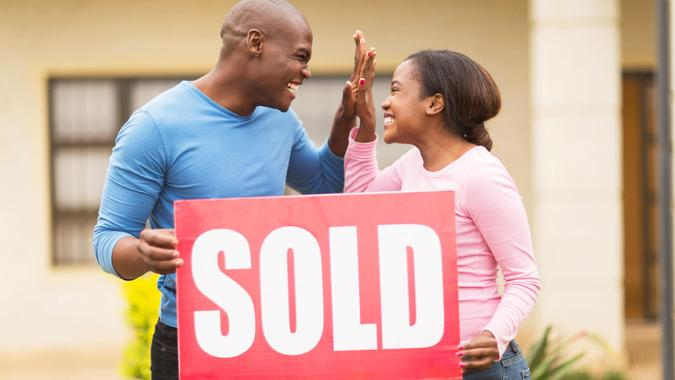 cheerful young african couple holding sold sign and celebrating their house been sold.