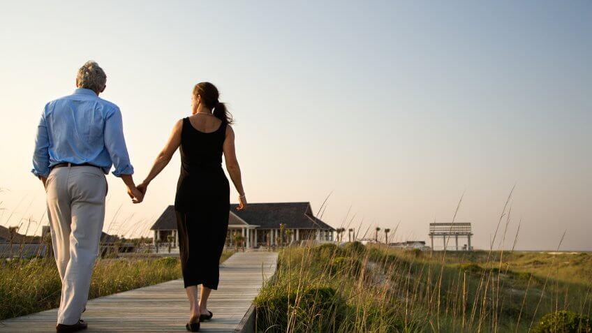 Couple walk hand in hand on a boardwalk towards a beach pavilion.