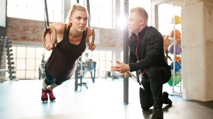 Young woman is doing exercises with the help of a personal trainer in a modern gym.