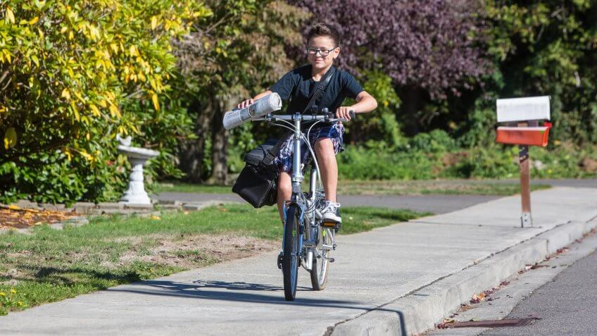 A young boy delivering newspapers on his bicycle.