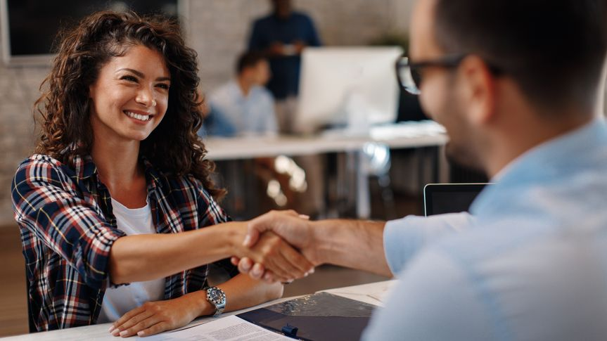 Young woman signing contracts and handshake with a manager.