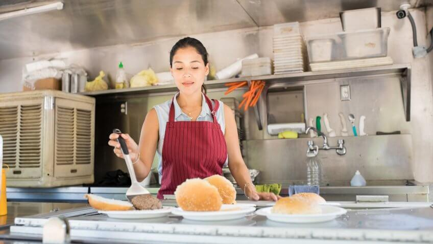 Attractive young woman with an apron working in a food truck and preparing a few burgers.