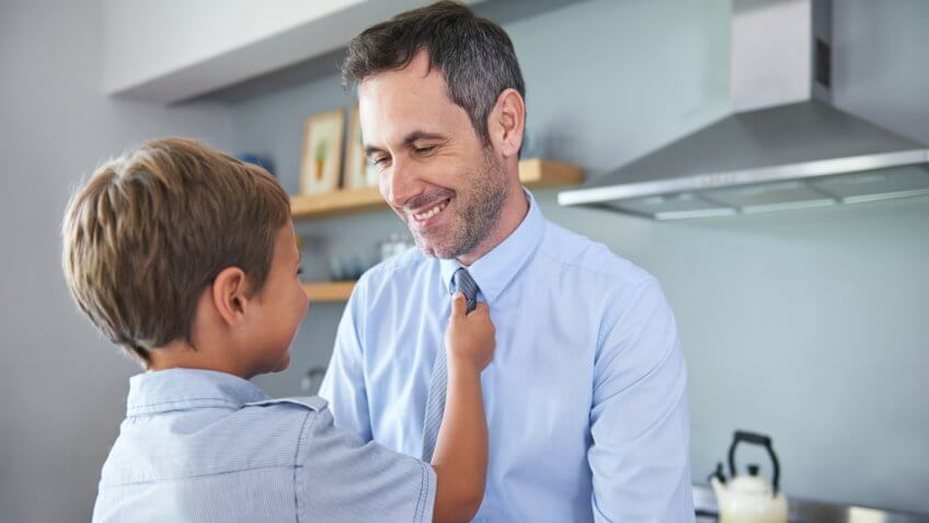 Shot of a little boy adjusting his father's neck tie in the kitchen.