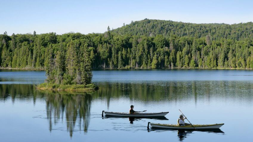 father and son kayaking on serene lake with bright sky (XXL).