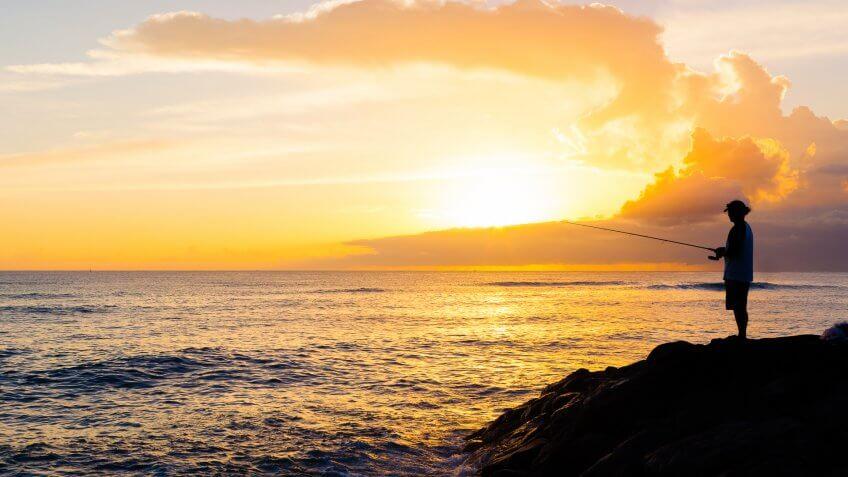 Man fishing during sunset.