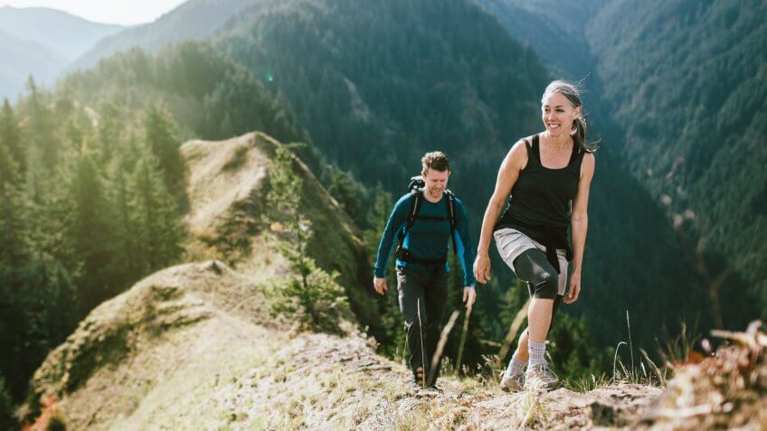 A fit man and woman in their 50's hiking the trail on a mountain ridge, the beautiful Columbia river gorge spreading out behind them.