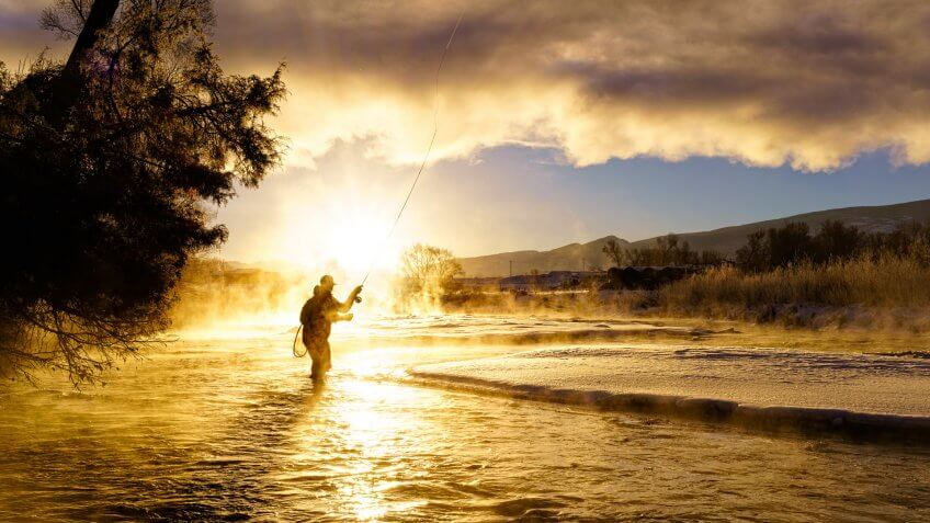 Fly Fishing in Winter at Sunrise - Scenic river with man fishing in cold temperatures.