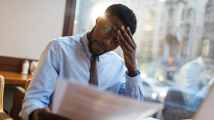 Focused African-American office manager sitting at cafe table with laptop, reading important documents with puzzled expression and holding head with his hand.