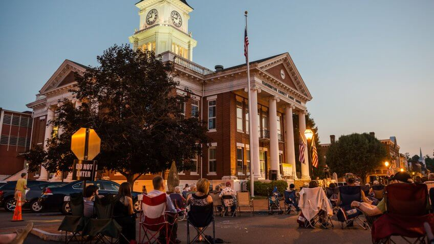 Jonesborough, Tennessee, USA - July 11, 2014: People gather with their outdoor chairs in front of the courthouse on Main Street in historic Jonesborough.
