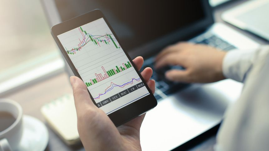 Hand holding smartphone with stock graph, surveying cheap stocks.
