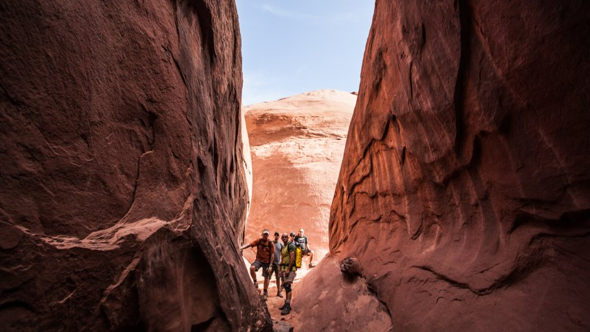 five men stand at the base of a slot canyon with sandstone walls and a clear blue sky beyond.