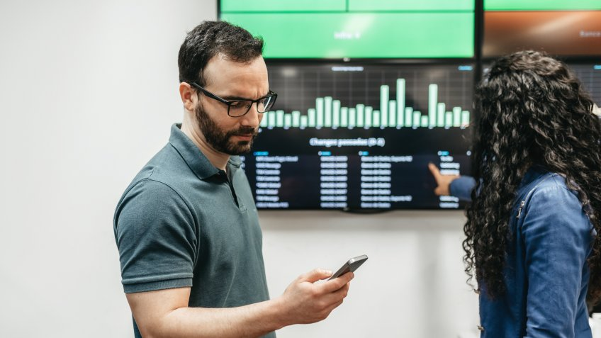 two young business people checking data on mobile and chart screen in office.