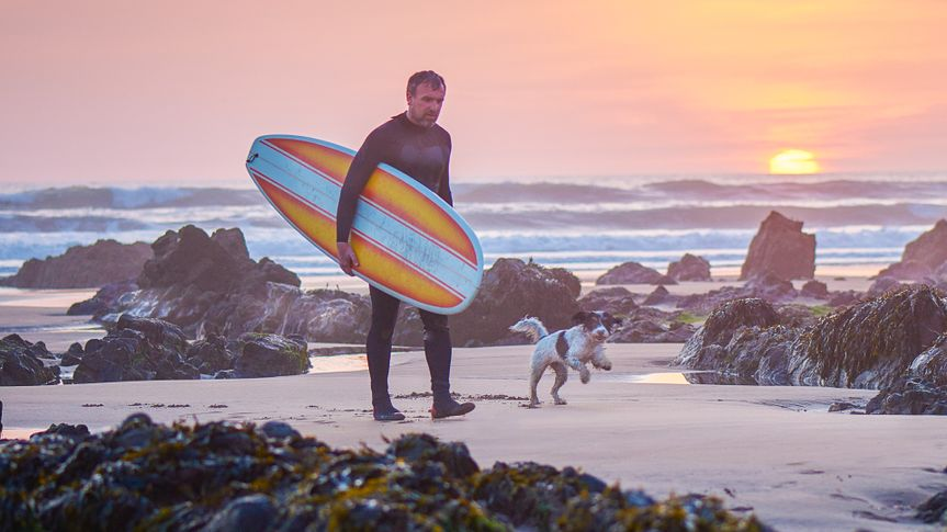 a mature man walks away from the sea at sunset  carrying his mini mal surfboard after a day's surfing .