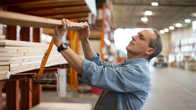 Adult male customer in hardware store choosing lumber for his home improvement project.