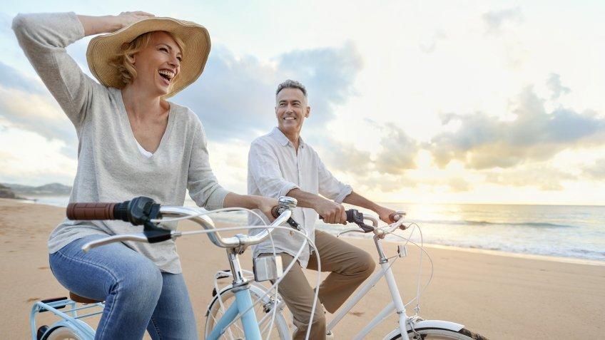 Mature couple cycling on the beach at sunset or sunrise.