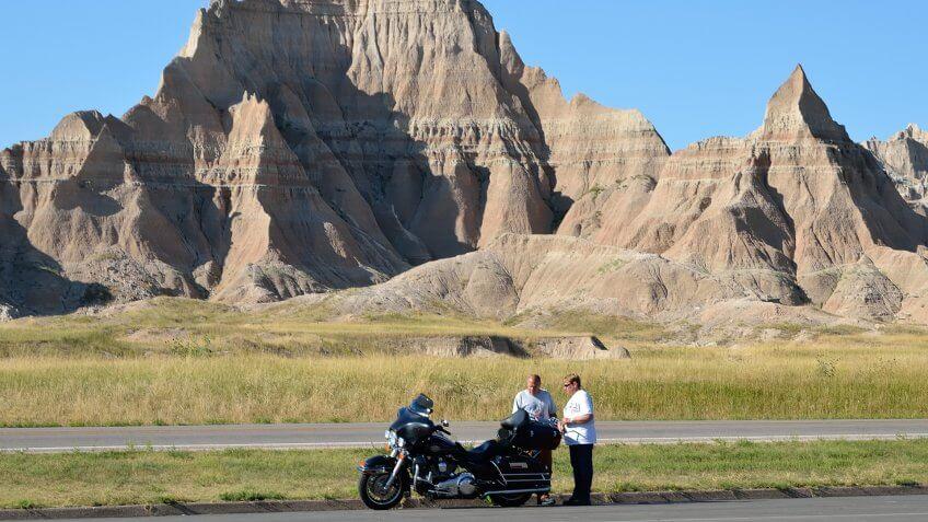 Badlands National Park, South Dakota, USA - September 5, 2011: Tourists taking a break against the rugged landscape of the Badlands National Park in South Dakota.