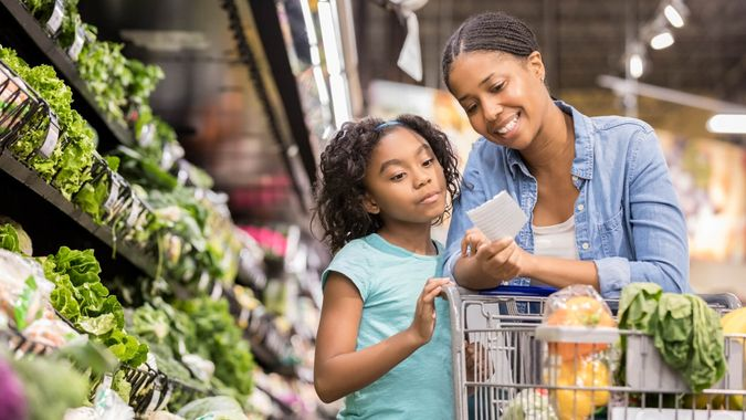 A smiling mid adult woman stands in the produce section of her supermarket and reaches down to show her serious elementary age daughter the next items on a paper shopping list.