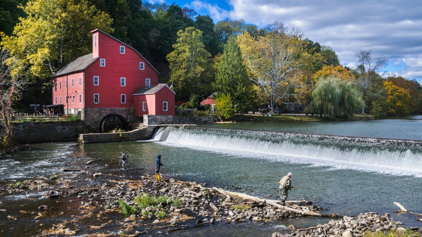 Clinton, New Jersey, USA - October 17, 2015: Three fishermen with rods, nets, and boots fish in the shallow waters below the dam at the Old Red Mill  on a crisp Autumn afternoon.